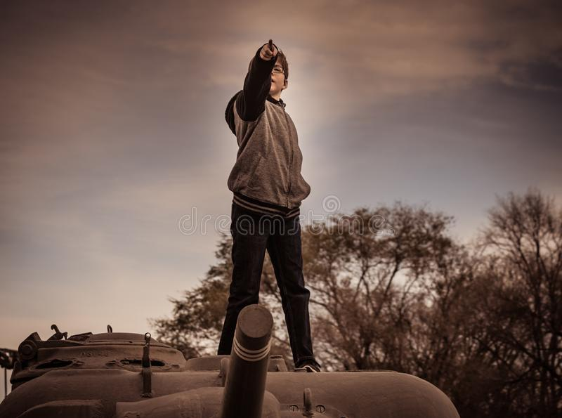 Boy Standing On Top of Army Tank royalty free stock photography