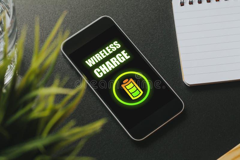 Charge sans fil dans un écran de téléphone portable au-dessus d'une table noire d'affaires photos libres de droits