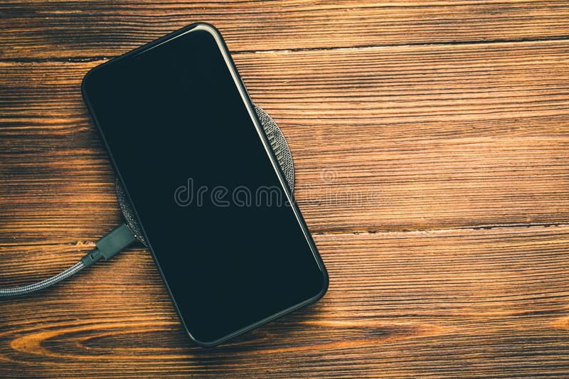 Charge your smartphone on the charging pad. Wireless charging on wooden table. rendered image royalty free stock photo