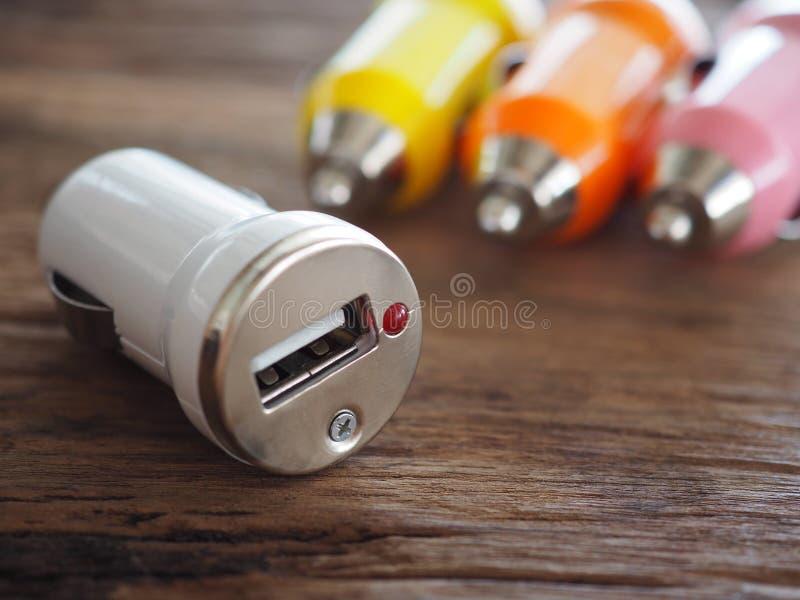 Chargeur coloré de voiture d'USB sur un conseil en bois avec le concept de technologie et d'énergie image stock