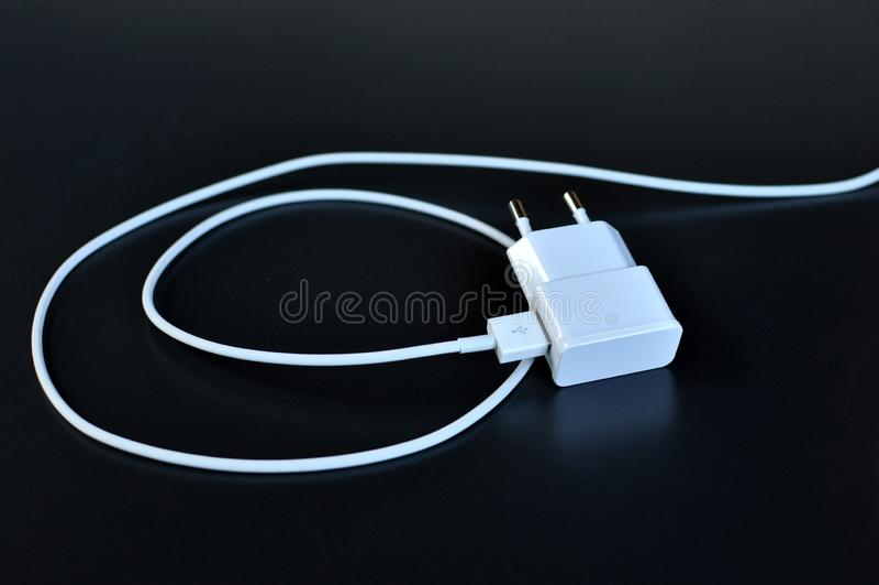 Chargeur de téléphone d'AWhite avec le câble et la prise blancs sur le fond noir photos libres de droits