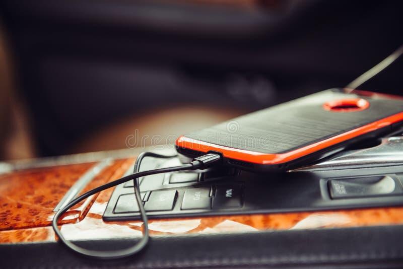Chargeur de voiture pour le téléphone portable Téléphone chargeant dans la voiture de luxe photos libres de droits