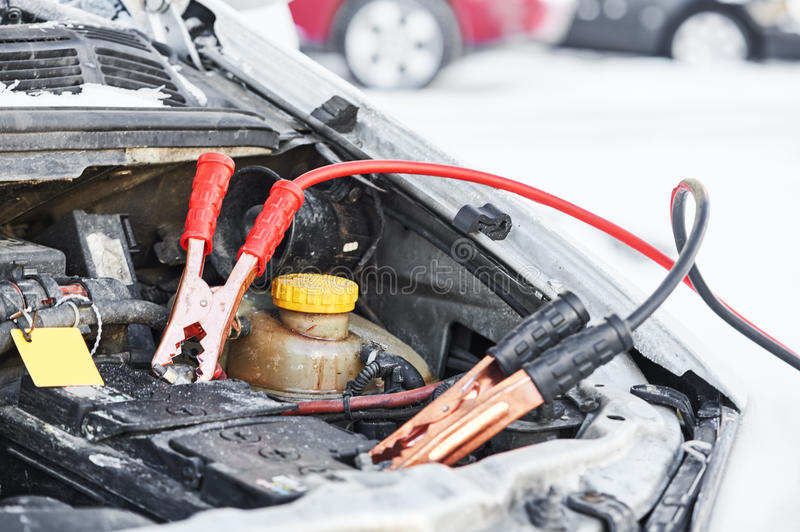 Charging automobile discharged battery by booster jumper cables at winter. Winter road assistance. Auto engine starting problem. Car battery discharged. Charging stock image