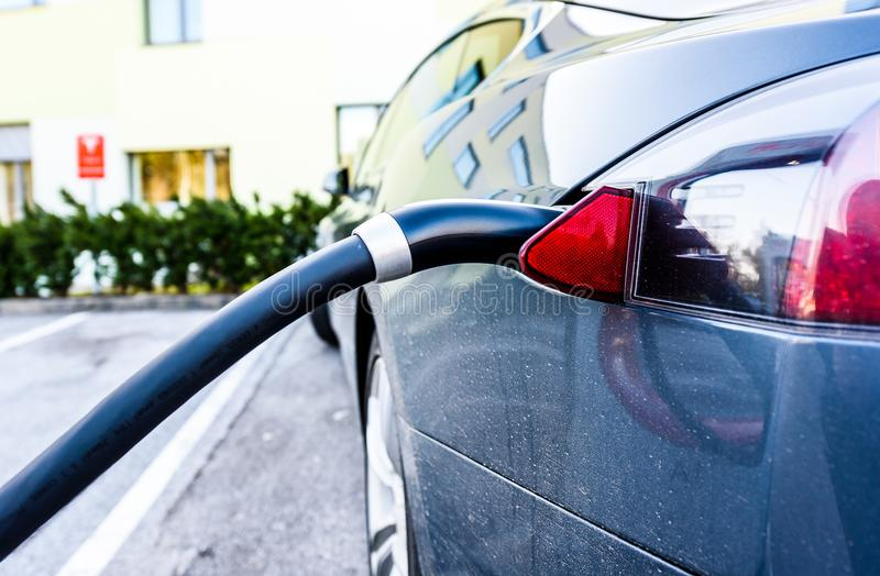 Charging electric car with black charging electric cable plugged stock photography