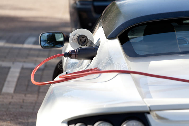 Charging of a electric sports car. Charging operation for electric Tesla Roadster in the city royalty free stock images