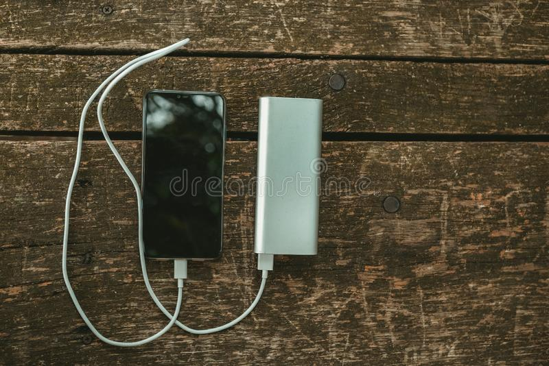 Charging the empty battery smartphone with white power bank. top view royalty free stock photography