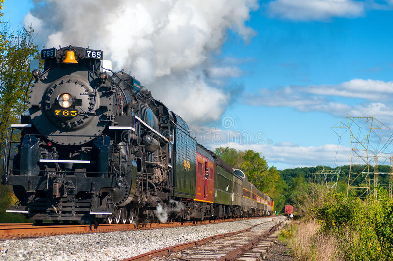 Charging locomotive. BRECKSVILLE, OH, USA - SEPTEMBER 14, 2013: The historic Nickel Plate 765 steam engine charges down the track as part of the annual Steam in stock image