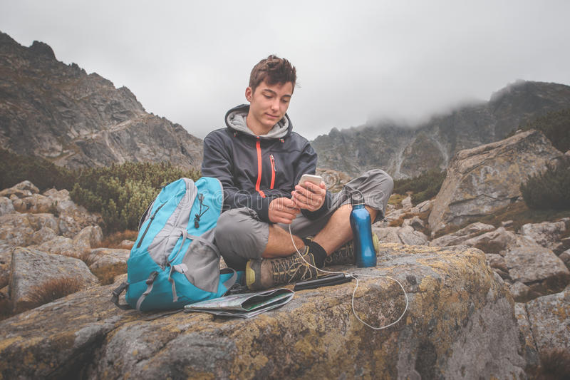 Charging a mobile phone on a mountain trail royalty free stock photos