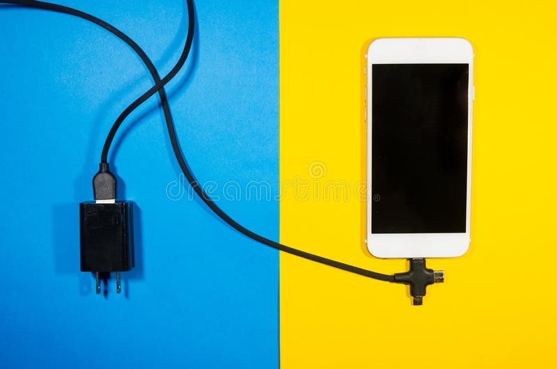 A charging phone connected with adapter block through black cable royalty free stock images