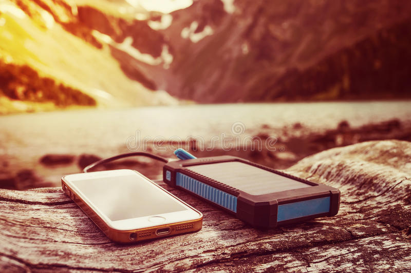 Charging smartphone phone from the solar battery. royalty free stock image