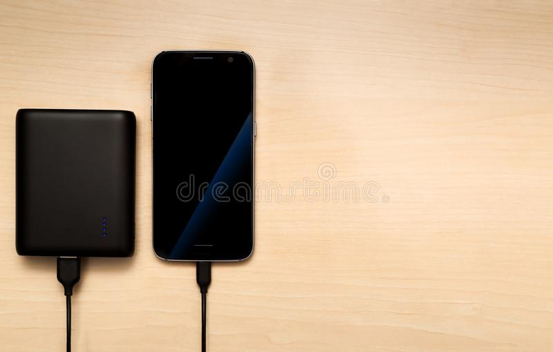 Charging smartphone with a power bank. On a wooden desk royalty free stock image