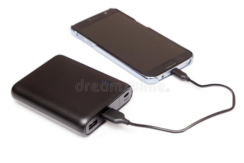 Charging smartphone with a power bank. On a wooden desk stock photo