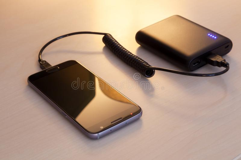 Charging smartphone with a power bank. On a wooden desk stock photos
