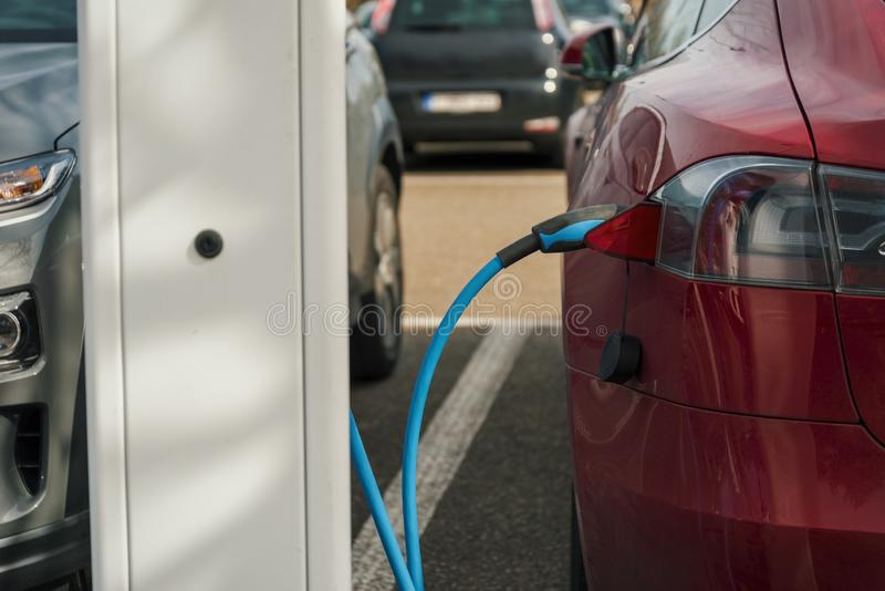 Close up of an electric car and a charging station royalty free stock image