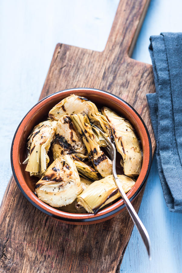 Chargrilled artichokes in ceramic bowl. From above on wooden board royalty free stock image