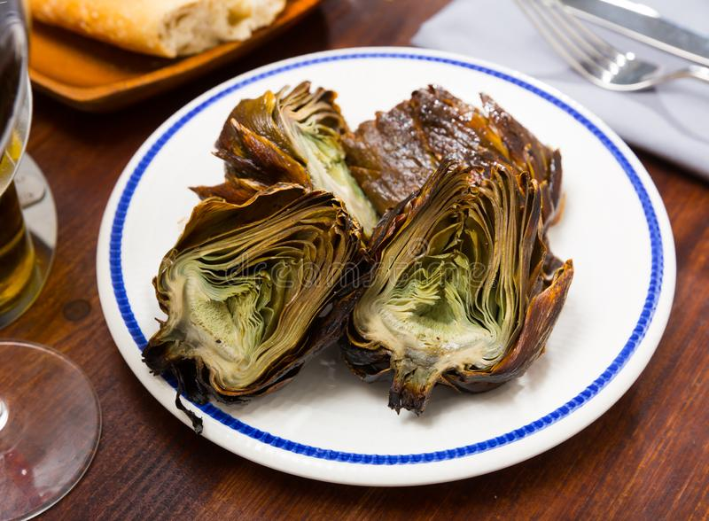 Chargrilled artichokes. Vegetarian appetizer of chargrilled artichokes served on white plate royalty free stock image