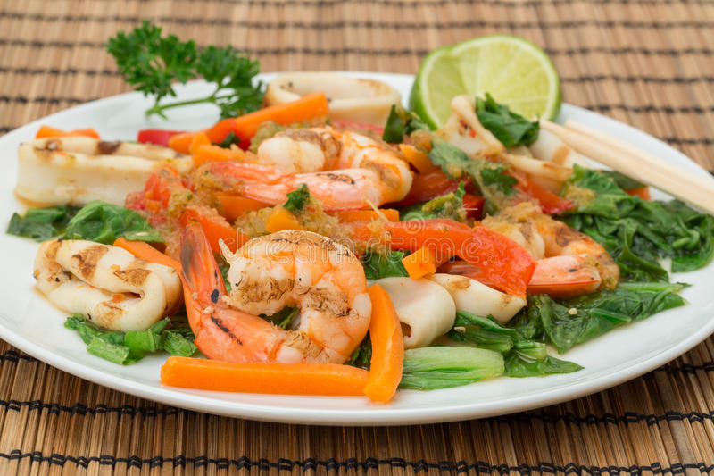 Chargrilled Calamari and KIng Prawns - Vietnamese cuisine. Vietnamese cuisine - plate of chargrilled Calamari and King Prawns with strips of carrot, red bell royalty free stock image