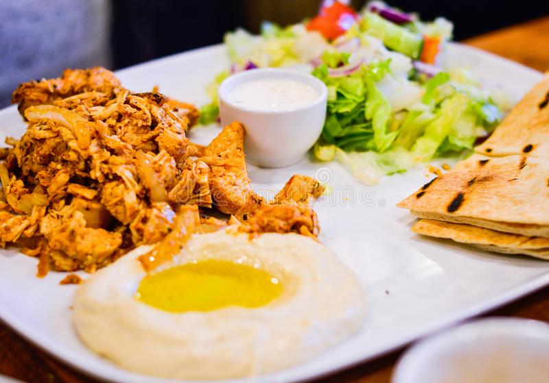 Chargrilled Marinated Chicken with Hummus, Pitta Bread and Salad. Authentic Middle Eastern Food from Restaurant royalty free stock image