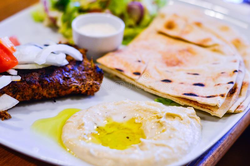 Chargrilled Minced Lamb with Hummus, Pitta Bread and Salad in White Plate. Authentic Middle Eastern Food from Restaurant stock photography