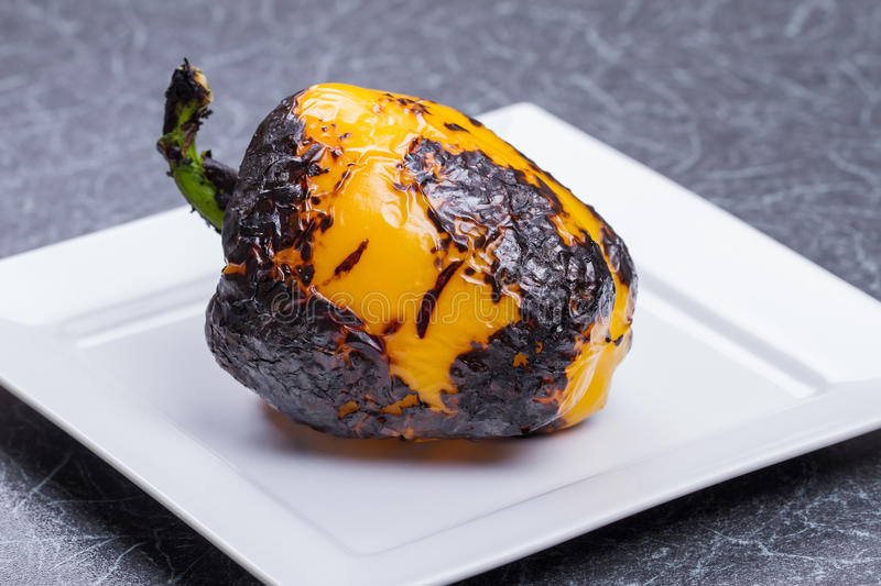 Chargrilled Pepper. A Whole Chargrilled Yellow Pepper on a White Plate royalty free stock image