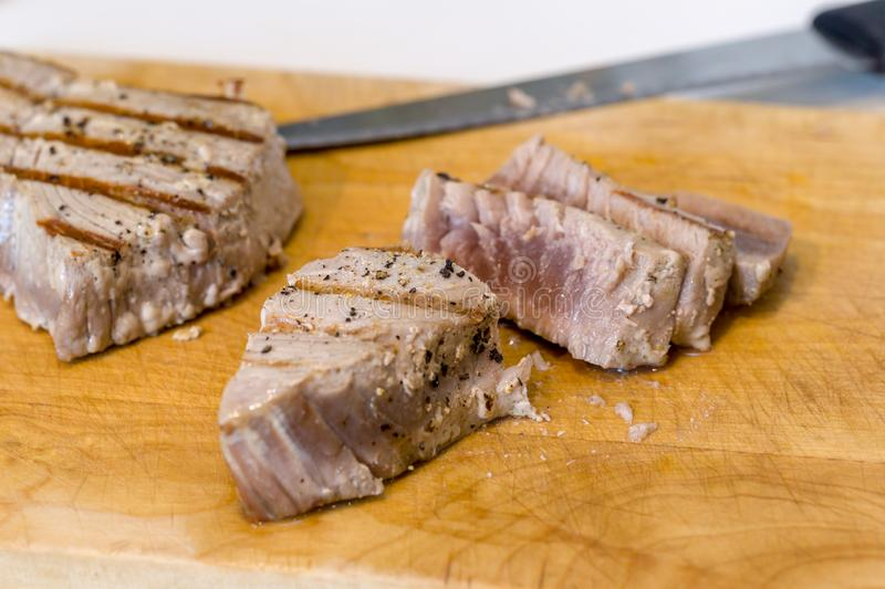 Chargrilled, seasoned tuna steaks. Cooked and sliced on a wooden chopping board stock photo