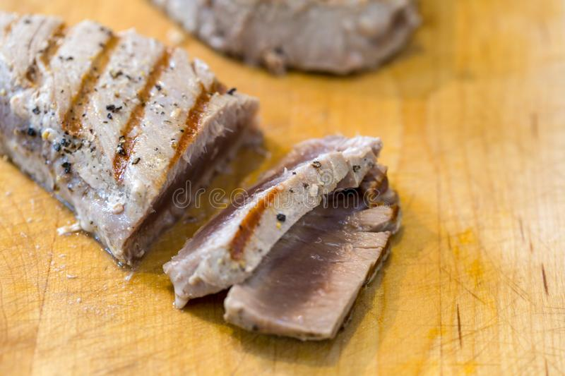 Chargrilled, seasoned tuna steaks. Cooked and sliced on a wooden chopping board royalty free stock image