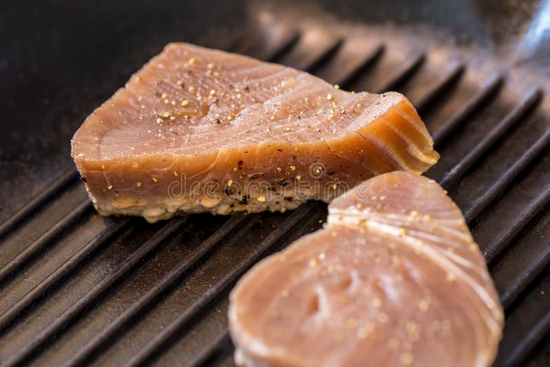 Chargrilled Tuna Steaks. Close up of chargrilled tuna steaks cooking in a griddle pan with seasoning royalty free stock photos