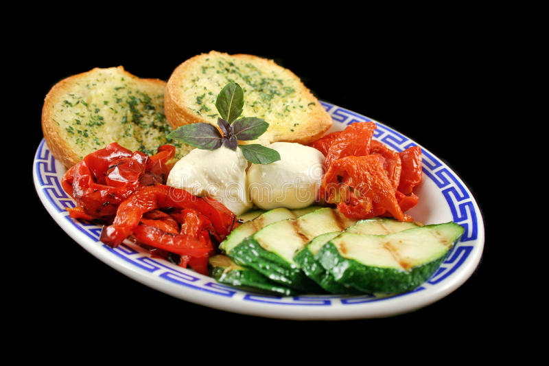 Chargrilled Vegetables. Delicious plate of chargrilled peppers, sundried tomatoes and zucchini with bocconcini cheese and herb bread royalty free stock photos