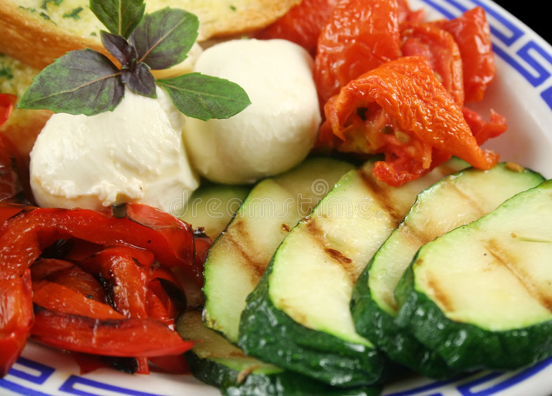 Chargrilled Vegetables. Delicious plate of chargrilled peppers, sundried tomatoes and zucchini with bocconcini cheese and herb bread stock images
