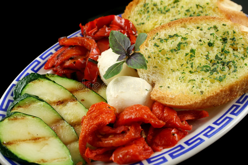 Chargrilled Vegetables. Delicious plate of chargrilled peppers, sundried tomatoes and zucchini with bocconcini cheese and herb bread stock photo