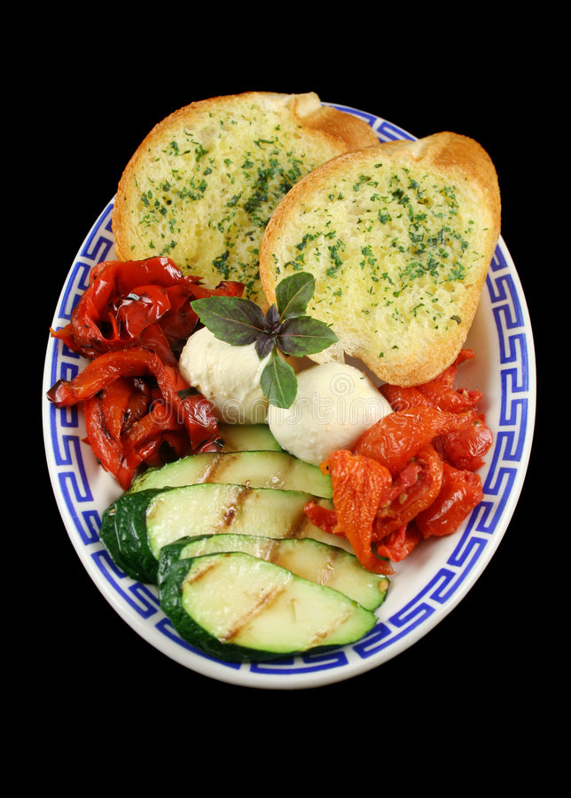 Chargrilled Vegetables. Delicious plate of chargrilled peppers, sundried tomatoes and zucchini with bocconcini cheese and herb bread stock image