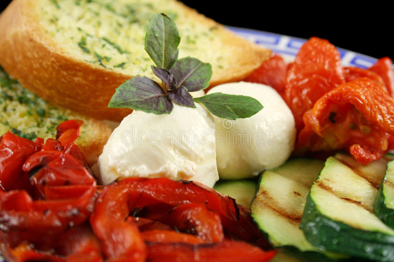 Chargrilled Vegetables With Cheese. Delicious plate of chargrilled peppers, sundried tomatoes and zucchini with bocconcini cheese and herb bread stock photography