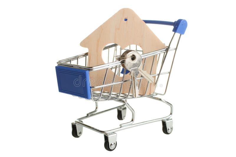 Chariot à épicerie avec la maison en bois décorative photos stock