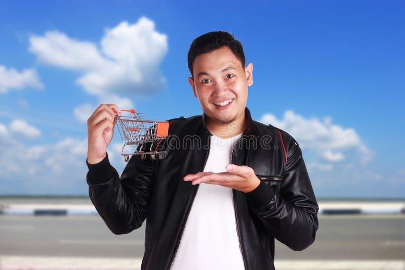 Chariot à achats de prise d'homme, concept de commerce électronique photo stock