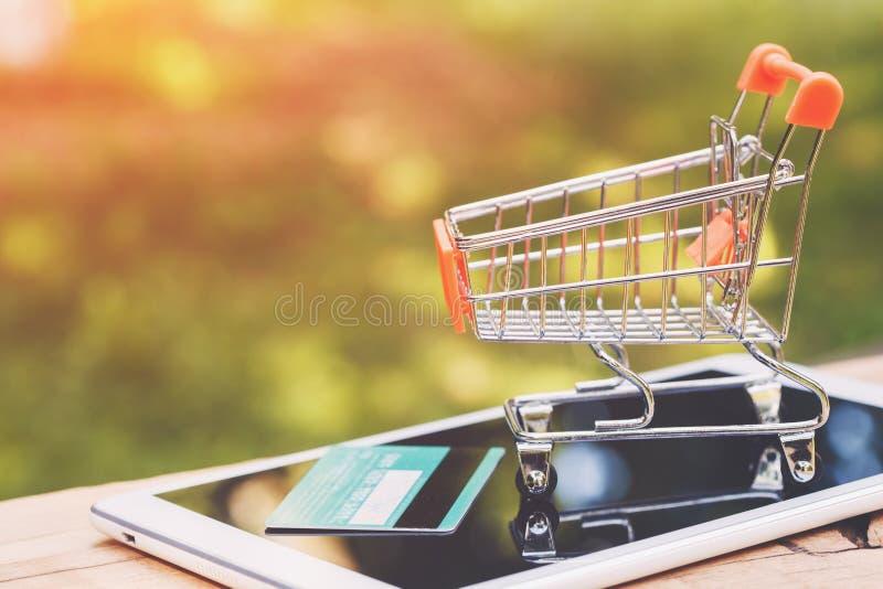 Chariot à jouet, carte de crédit et comprimé numérique sur la table en bois, l'espace de copie, concept de achat en ligne photos stock
