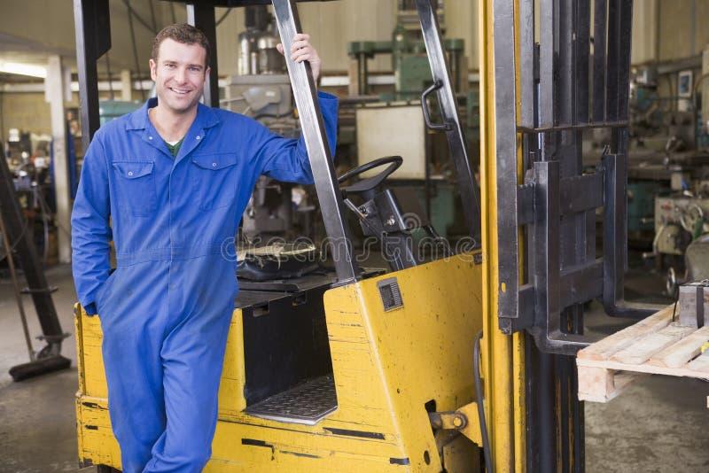 Chariot élévateur se tenant prêt d'ouvrier d'entrepôt image stock