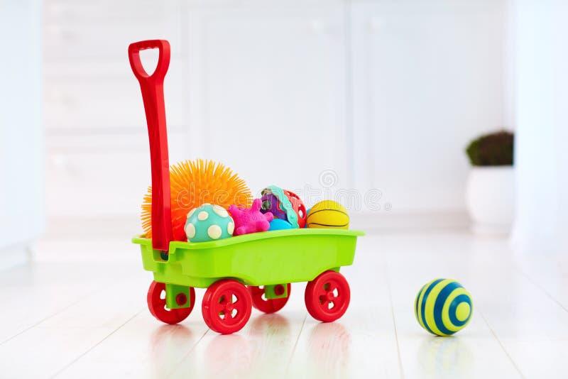 Chariot coloré à jouet complètement de différentes boules tactiles de couleur et de forme pour le développement du ` s d'enfant photographie stock libre de droits