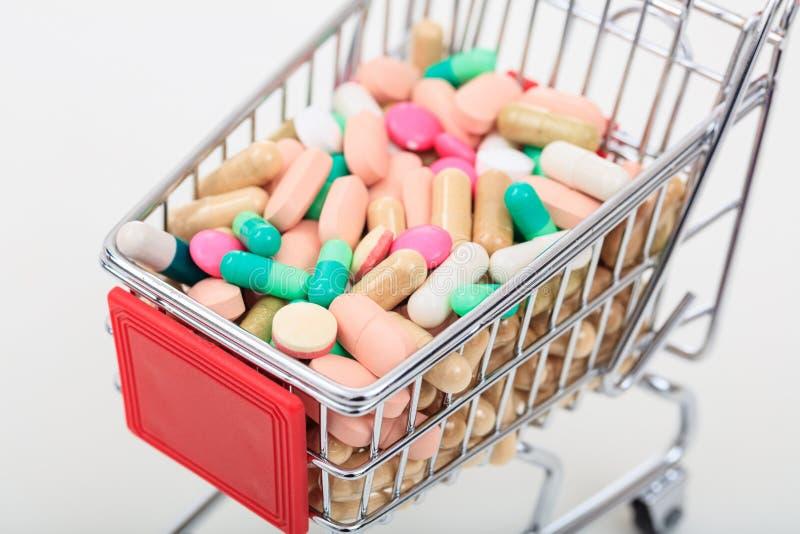 Chariot complètement des pilules sur le fond blanc images stock