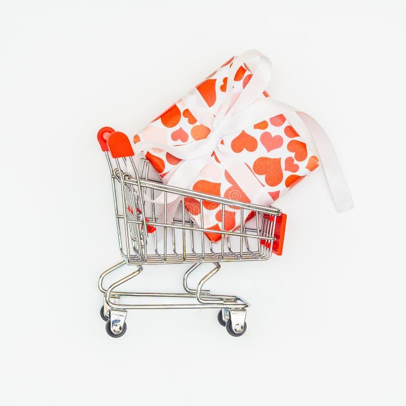 Chariot de achat avec des boîte-cadeau de coeurs sur le fond blanc images stock