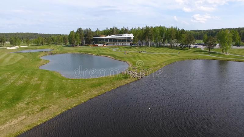 Chariot de golf solaire avec des nuages sur le ciel bleu et le club de golf de lac de forêt, aériens photographie stock libre de droits