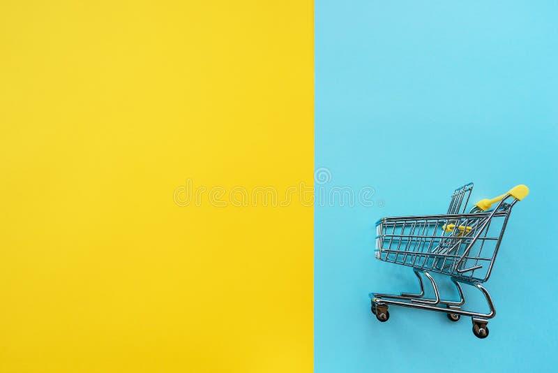 Chariot de jouet pour des produits sur un fond jaune-bleu de deux couleurs photographie stock libre de droits