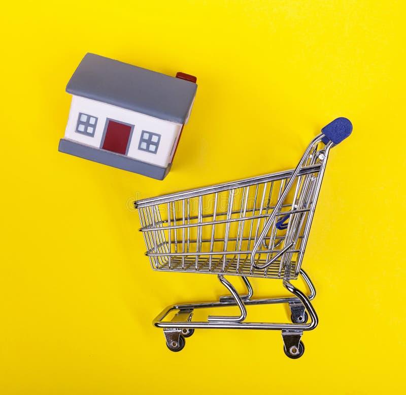 Chariot de Shoping avec les maisons en caoutchouc sur un fond jaune photo stock