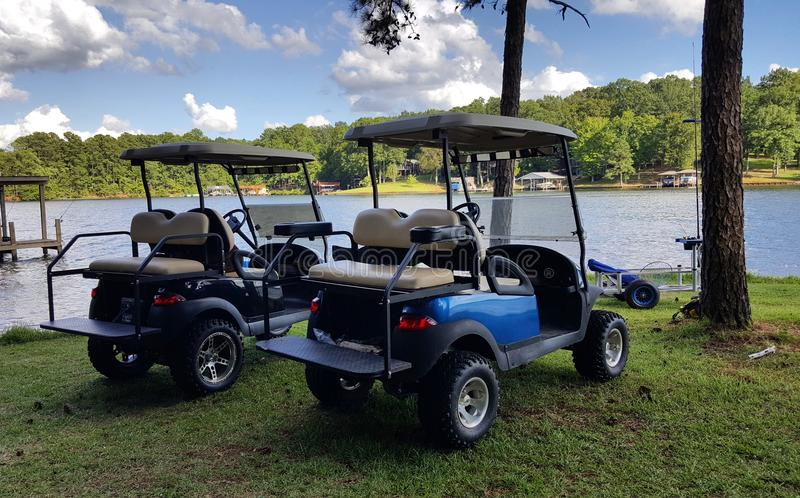 Chariots de golf par le lac images libres de droits
