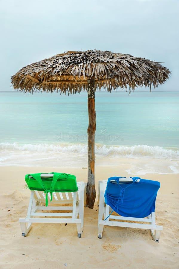 Charis van het strand en een strohut op het Cubaanse strand stock fotografie