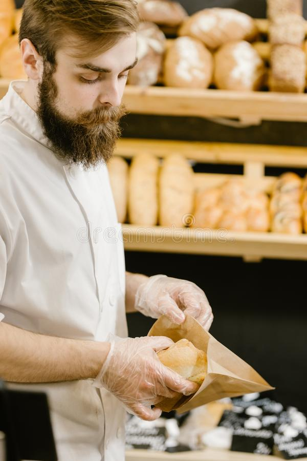Charismatic baker with a beard and mustache puts fresh bread in a paper bag in the bakery royalty free stock images