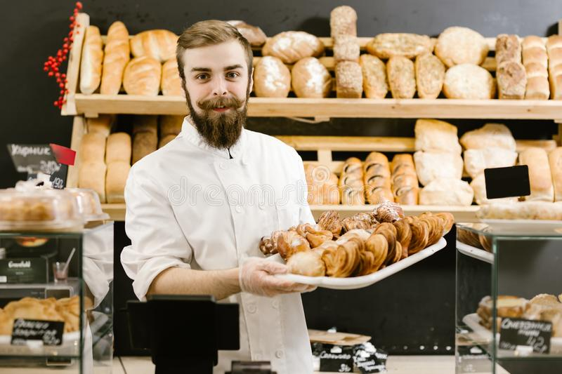 Charismatic baker with a beard and mustache stands with a tray with fresh pastries on the background of shelves with stock images