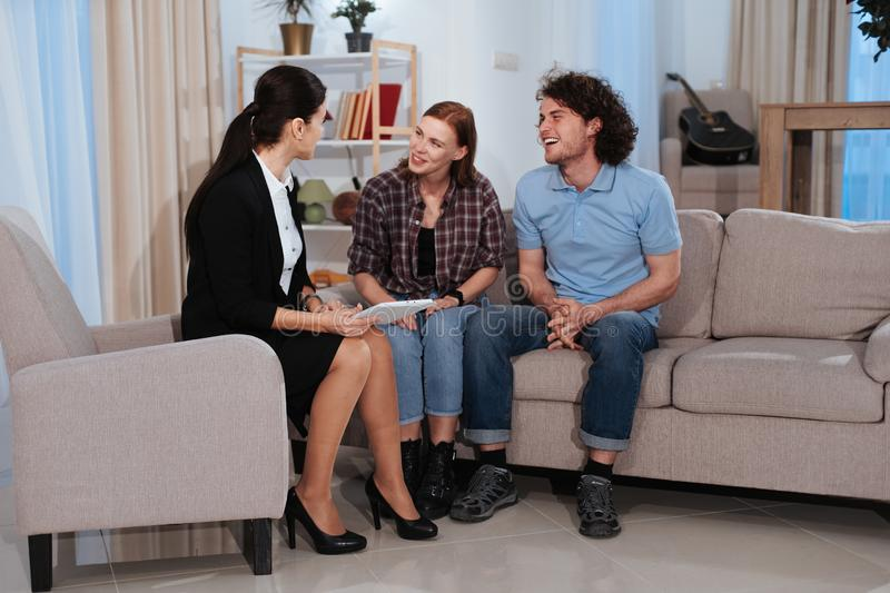Charismatic couple have a discussion with a real estate agent representing the house plan at the end she make a great royalty free stock images