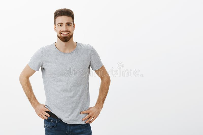 Charismatic friendly-looking and enthusiastic charming man suggesting his help holding hands on waist in self-assured. Pose smiling broadly waiting for command royalty free stock image
