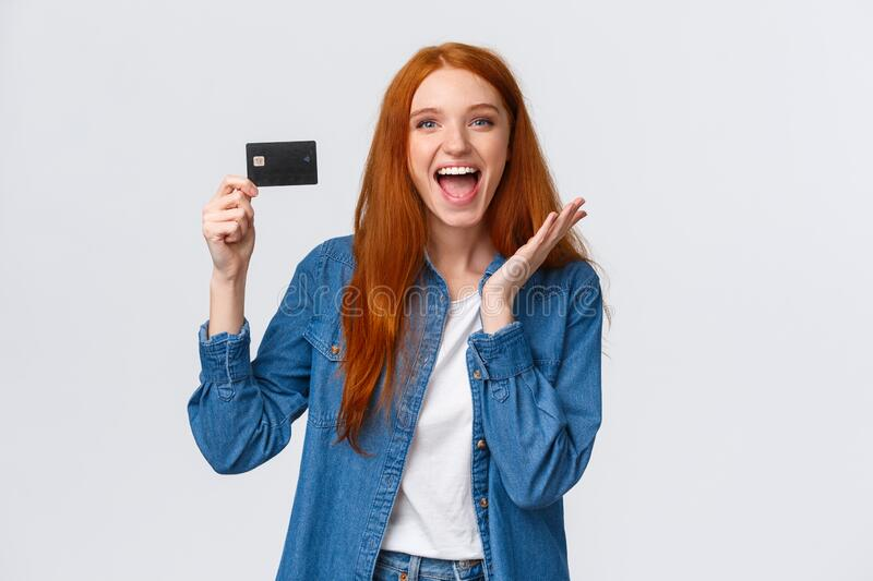 Charismatic happy good-looking redhead female student in casual clothes, holding credit card with beaming smile on face. Astonished and pleased, receive salary stock images