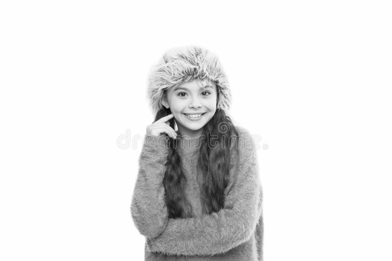 Charismatic kid girl wear hat with ear flaps white background. Soft furry accessory. Caring fur garments. Child long stock photography